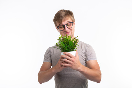 Nature, fun, fool around and nerd concept - Portrait of funny young man holding a plant over the white background