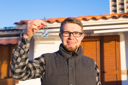 Dwelling, buying home, real estate and ownership concept - handsome man showing his key to new home Standard-Bild