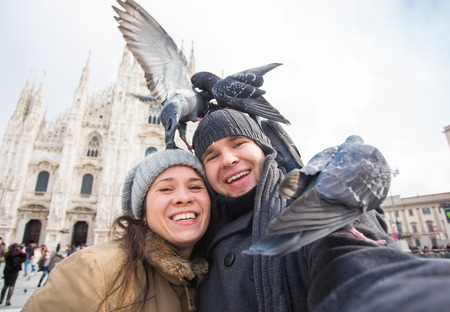 Couple taking self portrait with pigeon in Duomo square in Milan. Winter traveling, Italy and relationship concept Banco de Imagens - 118677889