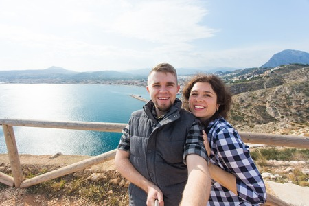 Travel, vacation and holiday concept - Happy couple taking selfie over beautiful landscape