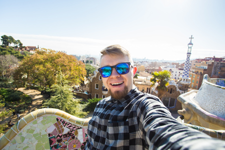 Travel and holidays concept - Happy guy making selfie portrait with smartphone in Park Guell, Barcelona, Spain.