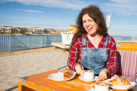 Young woman having breakfast with croissant and coffee at the cafe on the street in front of sea Imagens