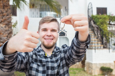 Property, ownership, new home and people concept - young man with keys standing outside new home