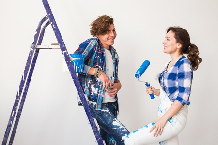 People, renovation and repair concept - Portrait of lovely couple doing redecoration in apartment