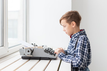 people, children and style concept - young boy with old black typewriter on white background.