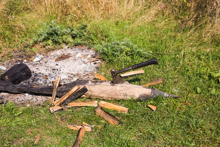 A pile of logs for a fire with a long handled axe embedded in a log ready for use