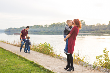 Family and children concept - mother, father and two sons enjoying the summer time, playing near the river
