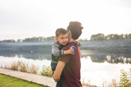 Fatherhood and children concept - Father holding his little son on nature