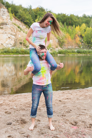 Festival holi, summer tourism and nature concept - young attractive girl sitting piggyback on her boyfriend on nature Stock Photo