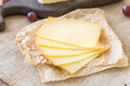 Close up of sliced cheese on rustic background