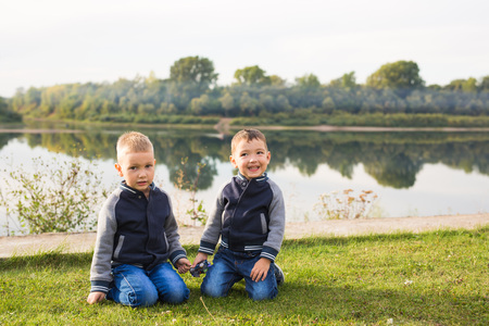 Children and nature concept - Two brothers sitting on the grass over nature background