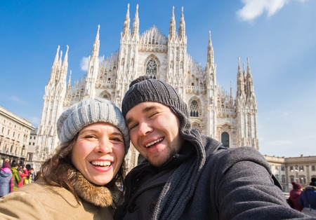 Funny couple taking self portrait in Duomo square in Milan. Winter traveling, Italy and relationship concept 版權商用圖片