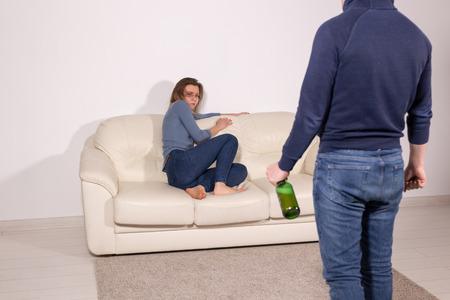 concept d'alcoolisme, de violence domestique et d'abus - l'homme se saoule à la maison et prend sa colère contre sa femme Banque d'images