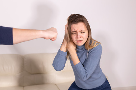 People, violence and abuse concept - man beating helpless woman at home background