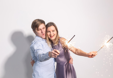 Party, family and holidays concept - young couple holding sparklers on white background