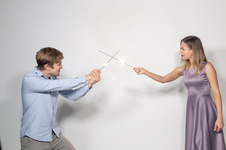 Holidays, party and celebrations concept - young funny happy couple with sparklers fooling around on white background