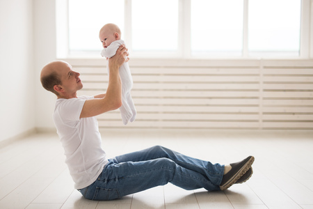 family, fatherhood and children concept - bald father holding cute newborn at home Фото со стока