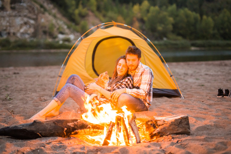 people, summer tourism and nature concept - couple near camp fire warming up seen from the tent Imagens
