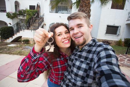 Nouvelle maison, immobilier et concept de déménagement - Un jeune couple amusant montre les clés de la nouvelle maison. Banque d'images