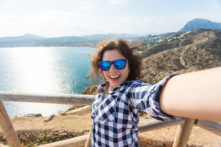 Travel, vacation and holiday concept - Happy young woman taking selfie over beautiful landscape Stock Photo - 118924669