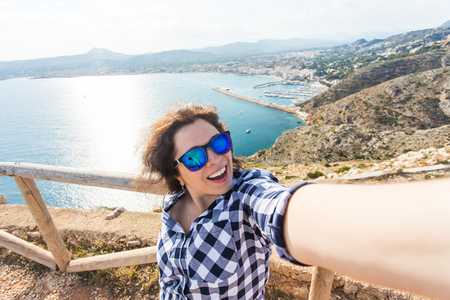 Travel, vacation and holiday concept - Young woman having fun, taking selfie, crazy emotional face and laughing.