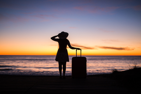 Travel, vacation and holiday concept - Young woman standing with suitcase on sandy beach at sea at the sunset