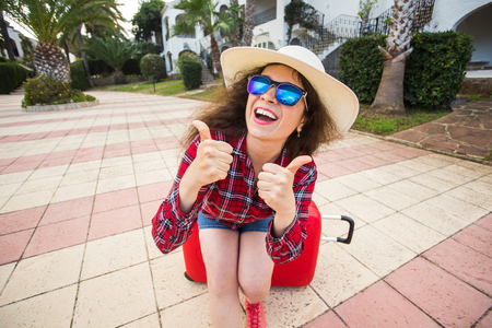 Travel, tourism and holidays concept - funny young woman sitting on red suitcase in glasses and hat showing thumb up and smiling