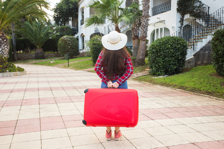 Travel, tourism and people concept - Back view of woman in hat carry a big red suitcase
