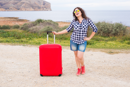 Travel, tourism and people concept - happy girl standing with red suitcase