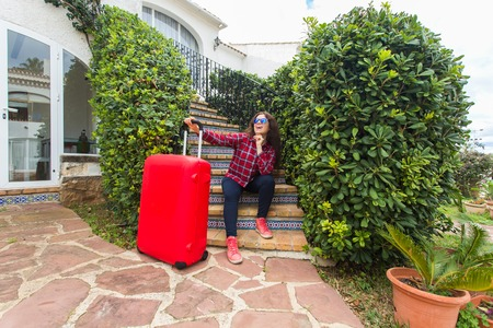Arrive, travelling and baggage concept - woman with luggage sitting near home door after voyage
