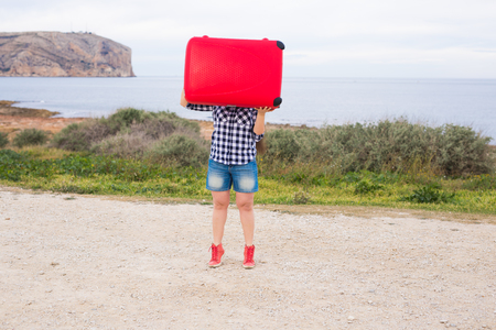 Holiday, travel and tourism concept - young woman with red suitcase over sea background
