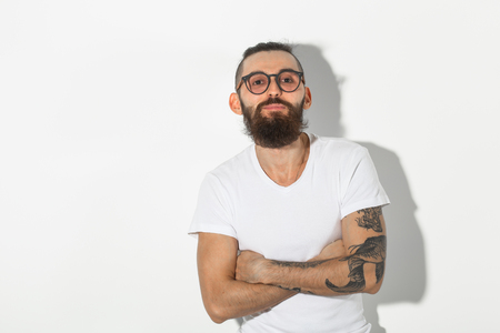 hipster, people concept - Skeptical hipster in white shirt with crossed arms
