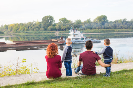 Parenthood, childhood and nature concept - Family sitting on the green ground and looking at small boat