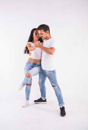 Passionate couple dancing social danse kizomba or bachata or semba or taraxia on white background Reklamní fotografie
