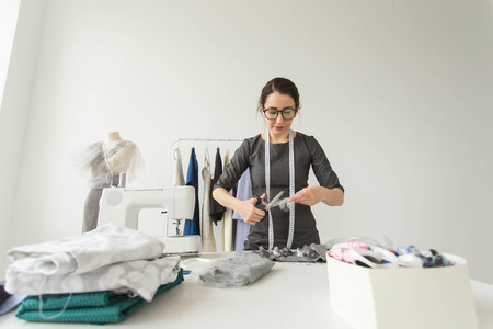 people, fashion and showroom concept - young fashion designer in her showroom