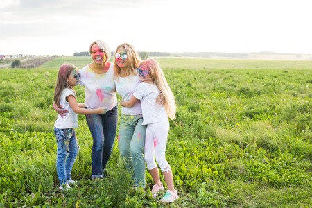 Friendship, Indian holidays and people concept - young women and children dancing on the summer field on festival of holi