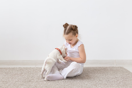 Pets owner, children and dogs concept - little girl sitting on the floor with cute Jack Russell Terrier puppy and playing Standard-Bild