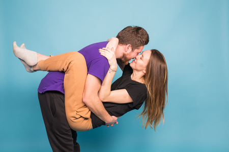 People, relationship and fun concept - Smiling man holding beautiful woman over blue background
