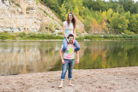 Festival holi, summer tourism and nature concept - young attractive girl sitting piggyback on her boyfriend on nature Stockfoto