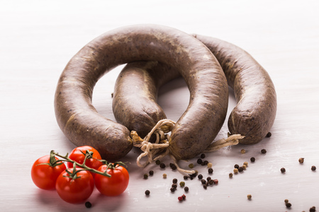 Food, meat and delicious concept - sausages made with horse meat with tomatoes on table. Stock Photo