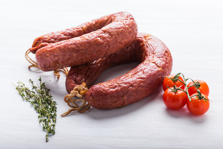 Food, national cuisine and delicious concept - Close up of traditional Kazakh horse meat sausage with tomato and cumin.