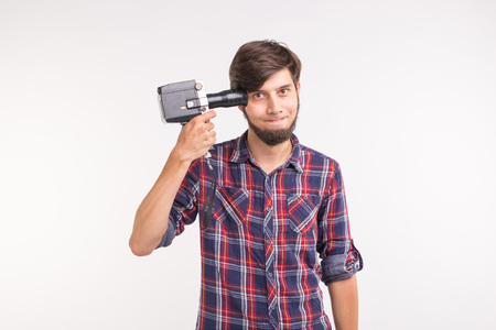 Joke, photo and gesture concept - young funny silly man posing with camera near his head on white background Imagens