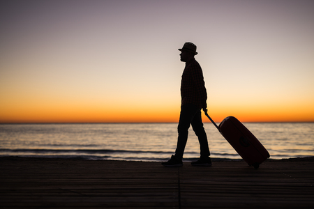 Vacation, holiday and travel concept - Silhouette of young man with suitcase on the beach at sunrise. Banco de Imagens
