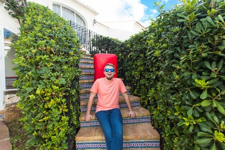 Travel, tourism and holidays concept - happy man sitting on stairs in sunny glasses holding the red suitcase