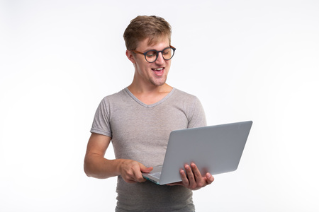 Emotions, education and people concept - a young handsome man looking in laptop and laughing