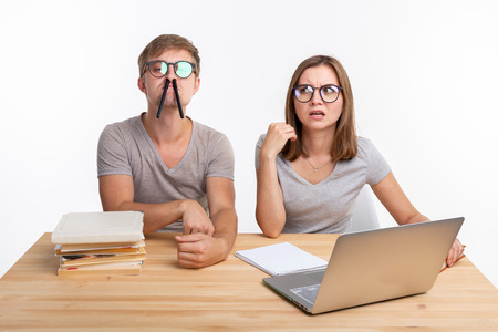 Education, fun and people concept - a couple of young people in glasses look like they are bored of learning homework and make a stupid jokes