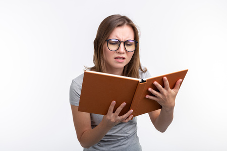 Study, education, people concept - female student is tired of learning classes, she is in gray shirt, standing with opened book