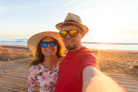Travel, vacation and holiday concept - Pretty young woman and her handsome boyfriend in straw hats make selfie Reklamní fotografie