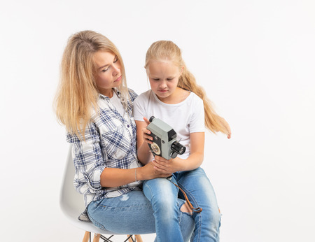 Family, photography and hobby concept - woman and her child using an old fashioned camera on white background