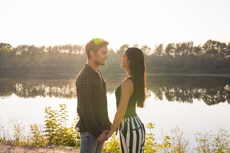 Love, romantic, nature, people concept - young lovely couple looking at each other and hugging near the lake